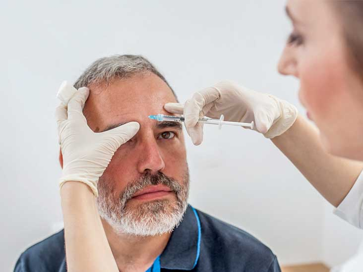 Doctor Applying Botox Therapy On Patient Face